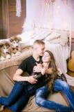 Pares de amor novos alegres que sentam-se no quarto ao expressar o amor com cachorrinhos fotografia de stock