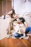 Pares de amor novos alegres que sentam-se no quarto ao expressar o amor com cachorrinhos imagens de stock royalty free