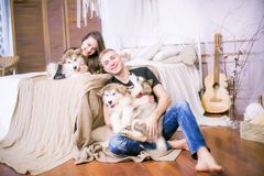 Pares de amor novos alegres que sentam-se no quarto ao expressar o amor com cachorrinhos imagem de stock royalty free