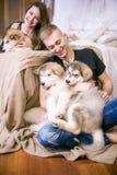 Pares de amor novos alegres que sentam-se no quarto ao expressar o amor com cachorrinhos foto de stock royalty free