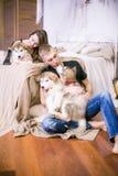 Pares de amor novos alegres que sentam-se no quarto ao expressar o amor com cachorrinhos imagens de stock
