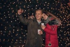 Pares de amor novos felizes que fazem o selfie com luzes no fundo fotografia de stock royalty free