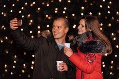 Pares de amor novos felizes que fazem o selfie com luzes no fundo foto de stock