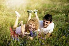 Pares de amor novos que apreciam a natureza, guardando as mãos e andando no campo com alfazema Povos bonitos na natureza na mola  fotografia de stock royalty free