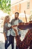 Pares de amor novos que apreciam o músico da rua com um violino fotografia de stock