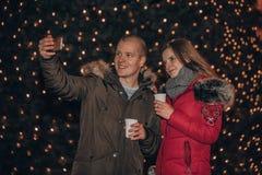 Pares de amor novos que fazem o selfie com luzes no fundo fotos de stock royalty free