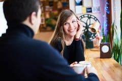 Pares de amor novos vestidos no estilo ocasional que senta-se em restaurantes pequenos no inverno e para beber o chá e o café que imagem de stock