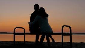 Pares de amor que se sientan en un banco en un abrazo en la playa y disfrutar de la puesta del sol almacen de video