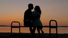 Pares de amor que sentam-se em um banco em um abraço na praia e para apreciar o por do sol filme