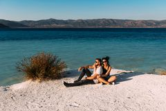 Pares de amor que sentam-se na borda do penhasco pelo mar Curso do casamento Viagem da lua de mel Menino e menina no mar imagens de stock