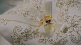 Pares de anéis de ouro do casamento no descanso branco tradicional pronto para a cerimônia de casamento video estoque