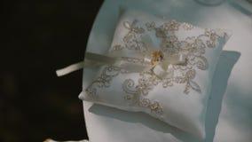 Pares de anéis de ouro do casamento no descanso branco tradicional pronto para a cerimônia de casamento filme