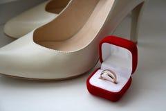 Pares de anillos de bodas en una caja y zapatos de la novia Foto de archivo libre de regalías