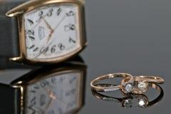 Pares de anillos de oro del ` s de las mujeres con los diamantes en un fondo del eleg Imagen de archivo libre de regalías
