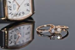 Pares de anillos de oro del ` s de las mujeres con los diamantes en un fondo del eleg Imágenes de archivo libres de regalías
