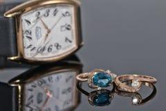 Pares de anillos de oro del ` s de las mujeres con los diamantes en un fondo del eleg Fotos de archivo libres de regalías
