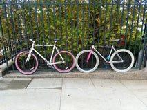 Pares de bicicletas coloridas estacionadas travadas à cerca foto de stock