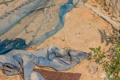 Pares de blue-jeans desvanecido que coloca na sujeira imagens de stock royalty free