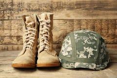 Pares de botas de combate y de casco militar en fondo de madera, foto de archivo libre de regalías