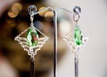 Pares de brincos de prata bonitos com as pedras preciosas no fundo natural Imagens de Stock