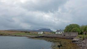 Pares de cabañas blancas en una costa costa escocesa remota rodeada fotografía de archivo