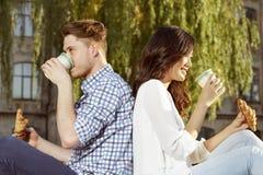 Pares de café del estudiante lindo y de cruasanes de consumición de la consumición Foto de archivo libre de regalías