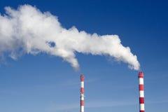 Pares de chaminés industriais com lote do fumo Fotografia de Stock Royalty Free