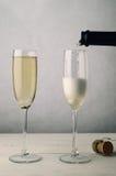 Pares de Champagne Glasses Being Filled acanelado na prancha de madeira Tabl Foto de Stock