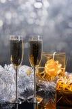 Pares de Champagne Glasses en la tabla con los regalos del oro Foto de archivo libre de regalías