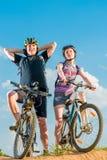 Pares de ciclistas nos capacetes em bicicletas Fotografia de Stock Royalty Free