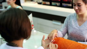 Pares de clientes de las mujeres que consiguen la manicura en salón moderno del clavo almacen de metraje de vídeo
