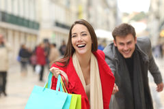 Pares de clientes que correm com sacos de compras fotos de stock