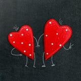 Pares de corazones en un tablero de tiza foto de archivo