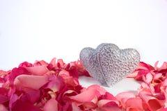 Pares de corazones tallados decorativos en pétalos color de rosa rojos imagenes de archivo