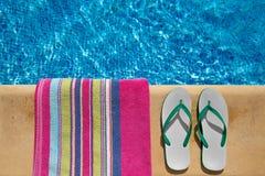 Pares de correas de la chancleta y de una toalla en el lado o Imágenes de archivo libres de regalías