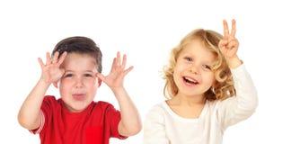 Pares de crianças que fazem gracejos Fotografia de Stock Royalty Free