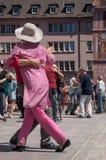 Pares de dançarinos do tango no lugar principal com outros dançarinos no festival do tango da mola Imagens de Stock