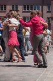 Pares de dançarinos do tango no lugar principal com outros dançarinos no festival do tango da mola Imagem de Stock Royalty Free