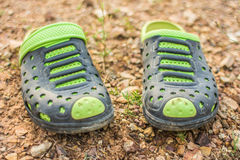 Pares de deslizadores verdes sujos no solo Fotografia de Stock Royalty Free