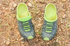 Pares de deslizadores verdes sujos no solo Foto de Stock Royalty Free