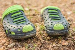 Pares de deslizadores verdes sujos no solo Imagem de Stock Royalty Free