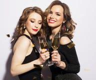 Pares de dois Rich Women Laughing com o cristal de Champagne luxo Party o tempo Imagem de Stock