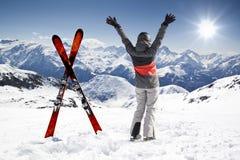 Pares de esquís cruzados con el esquiador de la mujer, manos para arriba Fotos de archivo libres de regalías