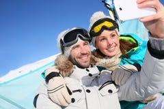 Pares de esquiadores que tomam o selfie ao tomar sol Imagens de Stock Royalty Free