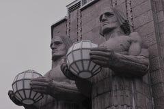 Pares de estátuas que guardam lâmpadas de rua na parede da estação de trem da central de Helsínquia foto de stock