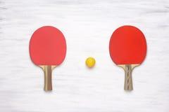 Pares de estafas de tenis de mesa en un fondo de madera imagen de archivo