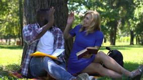 Pares de estudantes competidos misturados que fazem anotações e que olham no livro, doação alta-cinco video estoque
