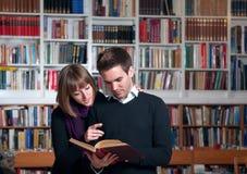 Pares de estudantes na biblioteca Fotografia de Stock Royalty Free