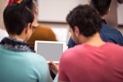 Pares de estudantes que olham a tabuleta na leitura Fotografia de Stock Royalty Free