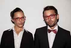 Pares de estudantes que vestem vidros vermelhos fotos de stock royalty free